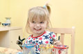 Happy toddler painting at the table a with paints and holding her messy hands up Stock Photography