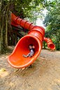 Happy toddler pre schooler sliding down red slide Royalty Free Stock Photo