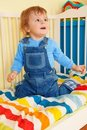 Happy toddler sitting in the baby cot Royalty Free Stock Image