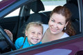 Happy toothy smiling mother with small daughter on driver seat inside of car Stock Photo