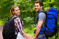 Happy tourist couple beautiful young loving carrying backpacks and looking over shoulder with smile while walking along the forest Stock Image
