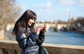 Happy tourist in paris sending an sms beautiful brunette Royalty Free Stock Photo