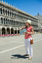 Happy tourist at san marco square in venice girl with map Stock Photo