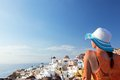 Happy tourist woman on santorini island greece travel in sun hat enjoying her holidays view caldera and aegean sea from oia Stock Photos