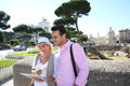 Happy tourists holding tablet during visit of rome couple using to capital Stock Photos