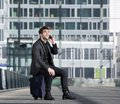 Happy travel man talking on mobile phone while sitting on suitcase Royalty Free Stock Photo