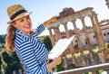 Happy traveller woman near Roman Forum holding map and pointing Royalty Free Stock Photo