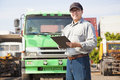 Happy truck driver writing on document a Stock Images