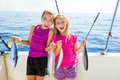 Happy tuna fisherwomen kid girls with fishes catch on boat trolling Royalty Free Stock Photos