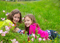 Happy twin sister girls playing on spring flowers meadow lying Royalty Free Stock Photography