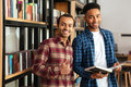 Happy two african men students standing in library reading books Royalty Free Stock Photo