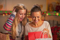 Happy two girlfriends exploring bags after shopping in kitchen christmas decorated Royalty Free Stock Image