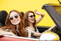 Happy two women friends sitting in car over yellow wall. Royalty Free Stock Photo