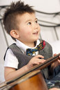 Happy two year old boy interested in arts and music fun loving young child strums the guitar smiling Royalty Free Stock Photo