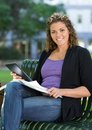 Happy university student with book studying on portrait of female and digital tablet sitting bench at campus Stock Photos