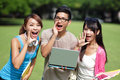 Happy university students shout and scream young using her hands on campus lawn asian Stock Images