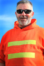 Happy unshaven laborer wearing sunglasses an older and an orange construction caution hooded sweat shirt blue sky background Stock Photo