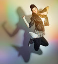Happy urban teenage girl jumping wearing black leather jacket and beanie hat pouting against colorful wall background and her Stock Photo