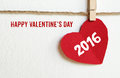 Happy valentine's day and red fabric heart shape hanging on cloth line background