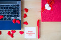 Happy Valentine`s day text written on white stickers, pc, red pen, gift box decorated by red hearts on wooden table in office. Royalty Free Stock Photo