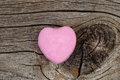 Happy Valentines day with single pink heart shaped candy on rust Royalty Free Stock Photo