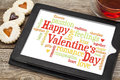 Happy valentines day word cloud on a digital tablet with heart cookies and a cup of tea Stock Images