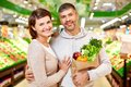 Happy vegetarians image of couple with paperbag full of products looking at camera in supermarket Royalty Free Stock Photos