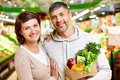 Happy vegetarians image of couple with paperbag full of products looking at camera in supermarket Royalty Free Stock Photography