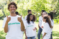 Happy volunteer gesturing thumbs up portrait of with friends disucssing in background Royalty Free Stock Image