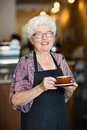 Happy waitress with coffee cup in cafeteria portrait of senior Royalty Free Stock Photography