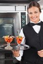 Happy waitress holding dessert tray portrait of in industrial kitchen Royalty Free Stock Image