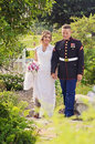 Happy wedding couple in garden a bride and groom military uniform walking Royalty Free Stock Photo