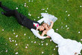 Happy wedding couple lying on green grass Royalty Free Stock Photo