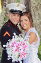 Happy wedding couple a newlywed portrait holding bouquet of flowers groom is military men in uniform Stock Photo