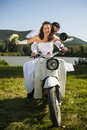 Happy wedding couple take a ride in a white motorcycle. Royalty Free Stock Photo