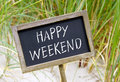 Happy weekend sign written on chalkboard or blackboard on beach with green grass in background Stock Photo