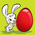 Happy white cute cartoon bunny presenting its huge easter egg Royalty Free Stock Images