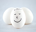 Happy white egg with smile three eggs one a printed on it Stock Image