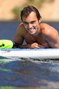 Happy windsurfer smiling take a rest on the board and Royalty Free Stock Photo