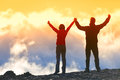 Happy winners reaching life goal success people at summit business achievement concept two person couple together arms up in the Stock Photo