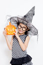 Happy witch child with pumpkin in halloween dress Stock Image