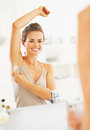 Happy woman applying roller deodorant on underarm in bathroom modern Royalty Free Stock Photography