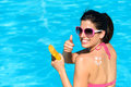 Happy woman applying sunscreen on summer funny or suntan lotion her back and sitting at poolside holidays and approving with Stock Images