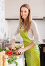 Happy woman in apron slicing vegetables kitchen Royalty Free Stock Photography