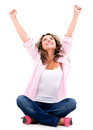 Happy woman with arms up sitting isolated over a white background Stock Photography