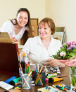 Happy woman artist with her admirer women select pictures Stock Photo
