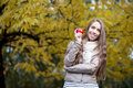 Happy woman in autumn park young casual caucasian smiling while holding red apple Royalty Free Stock Image