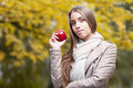 Happy woman in autumn park young casual caucasian smiling while holding red apple Royalty Free Stock Photos