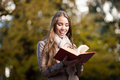 Happy woman in autumn park young casual caucasian smiling while holding red book Stock Photo