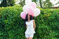 Happy woman with balloons near the green hedgerow outdoors Royalty Free Stock Images